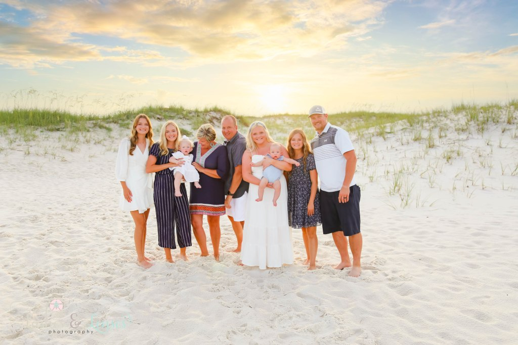Extended Family standing in front of sand dunes with the sunset behind them at Johnsons Beach in Perdido Key Florida