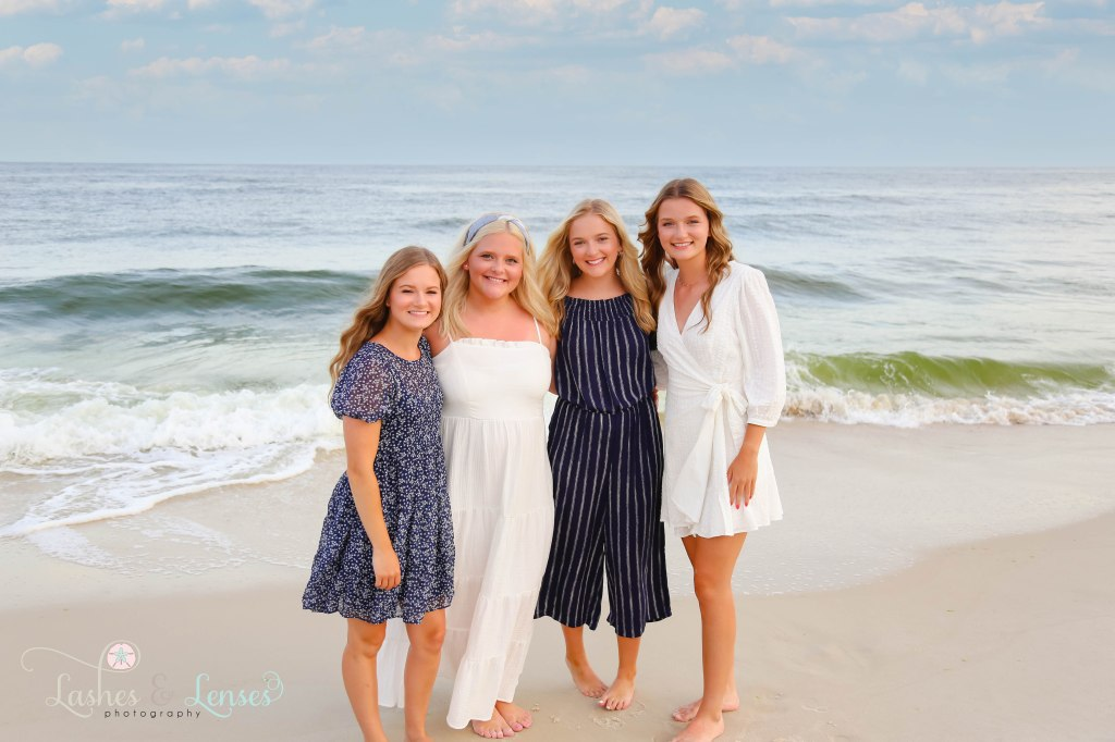 Four Adult sisters standing right at the edge of the water at Johnsons Beach in Perdido Key Florida