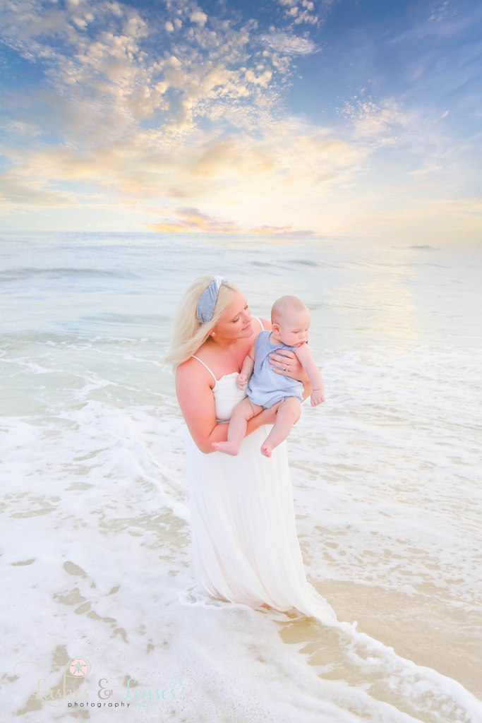 Mom standing in the water with the sunset behind her, holding and looking at her baby son at Johnsons Beach in Perdido Key Florida