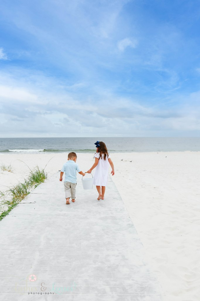 Brother and sister walking down the boardwalk towards the water and holding a bucket in between them Extended family all looking at little girl and standing next to a small sand dune at Johnsons Beach in Perdido Key Florida