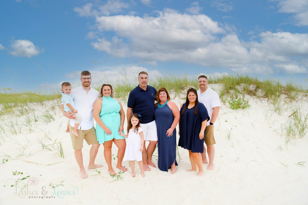 Extended family all looking at little girl and standing next to a small sand dune at Johnsons Beach in Perdido Key Florida