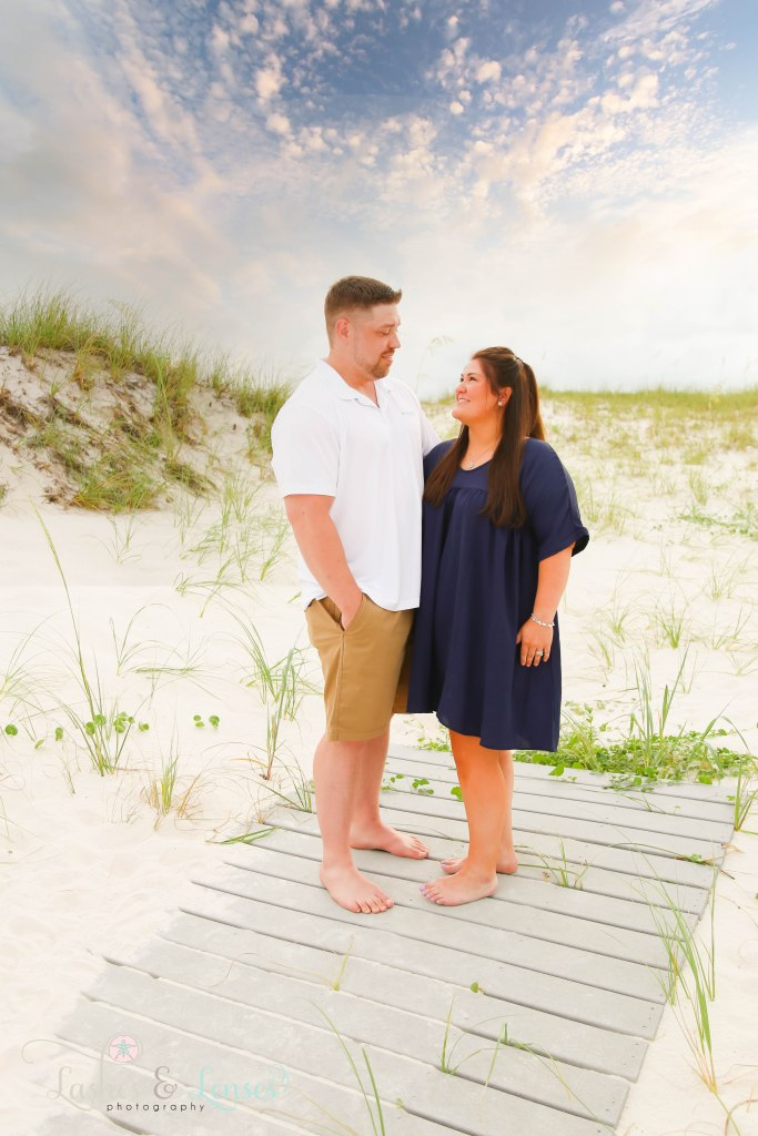 Husband and Wife standing on a washed up boardwalk with the sand dunes behind them at Johnsons Beach in Perdido Key Florida