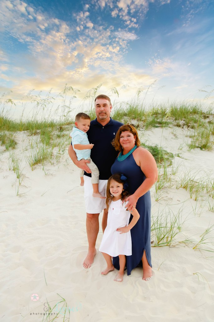 Grandma and Grandpa standing next to the sand dunes with their granddaughter and grandson at Johnsons Beach in Perdido Key Florida
