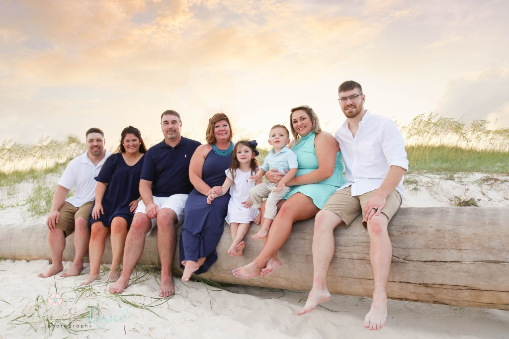 Extended family sitting on a washed up palm tree with the sunset behind them at Johnsons Beach in Perdido Key Florida