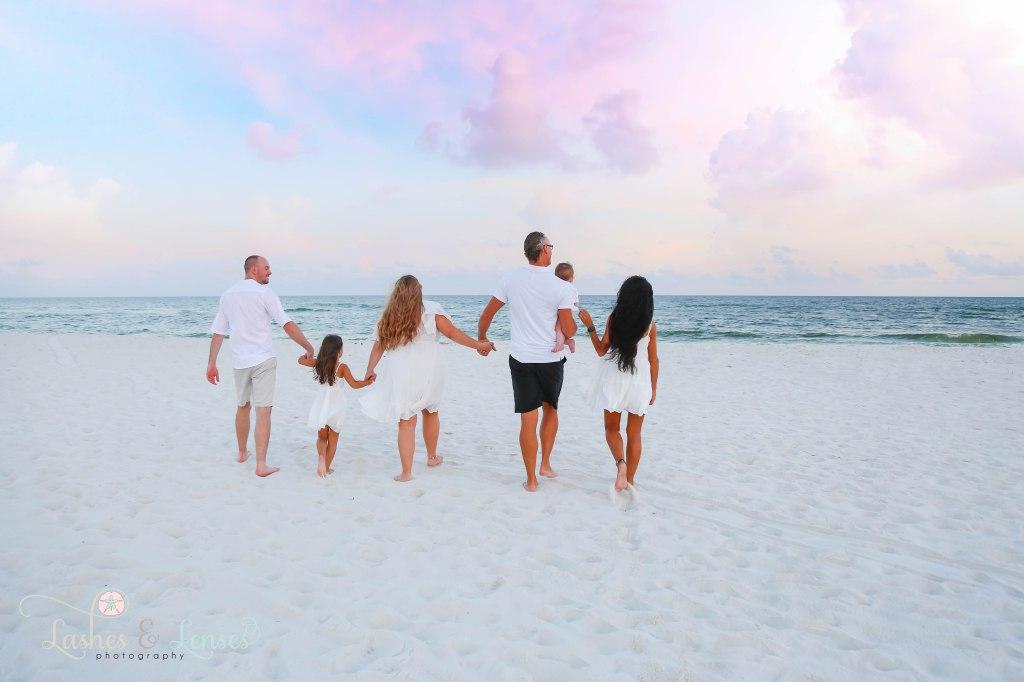 Family walking down the beach towards the water at Johnsons Beach in Perdido Key Florida
