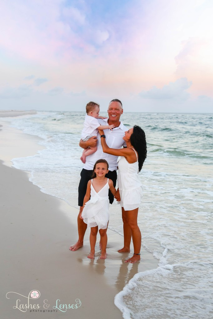 Grandparents with their granddaughter and grandson with the water hitting their feet at Johnsons Beach in Perdido Key Florida