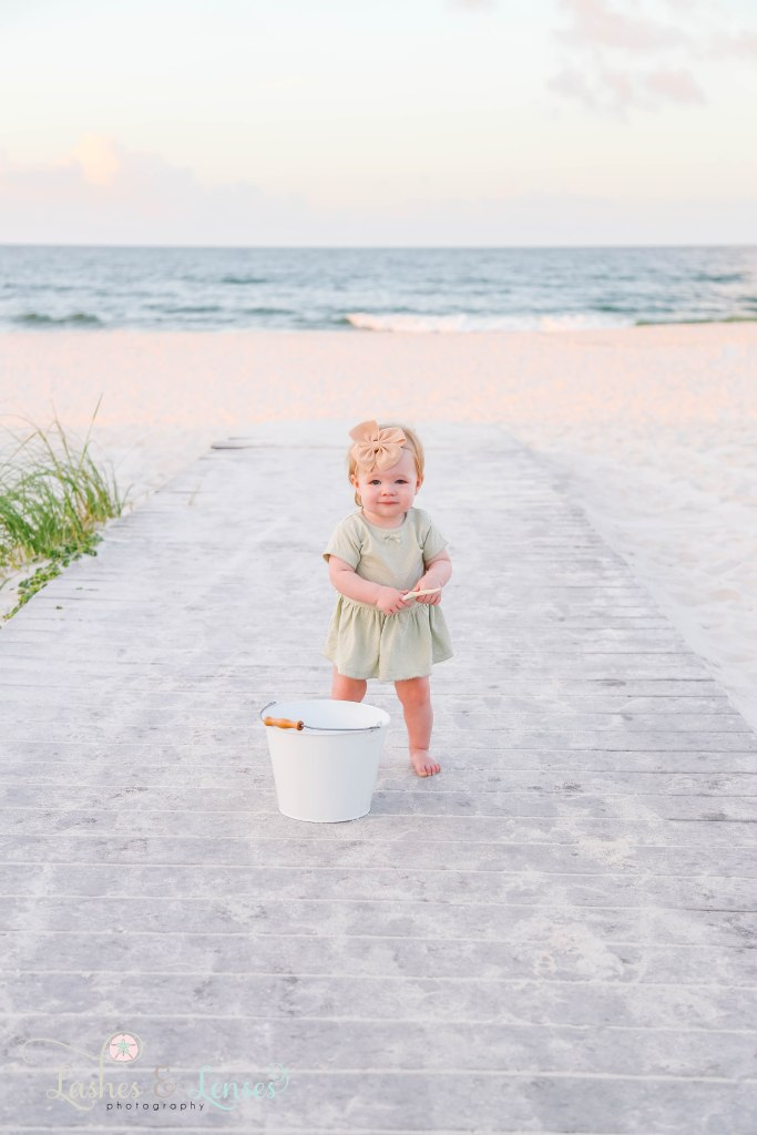 Baby girl standing on boardwalk with the water behind her and holding a starfish at Johnsons Beach in Perdido Key Florida