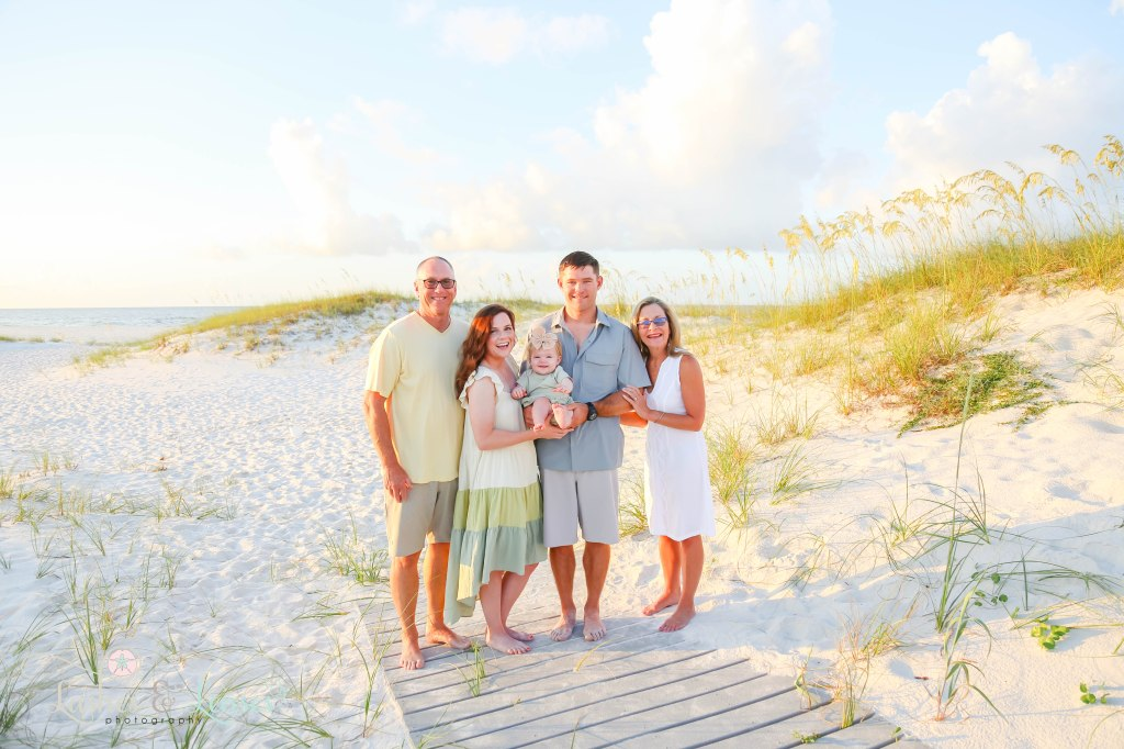 Grandparents, Mom and Dad and Baby girl standing on a washed up boardwalk with the sand dunes and water behind them at Johnsons Beach in Perdido Key Florida
