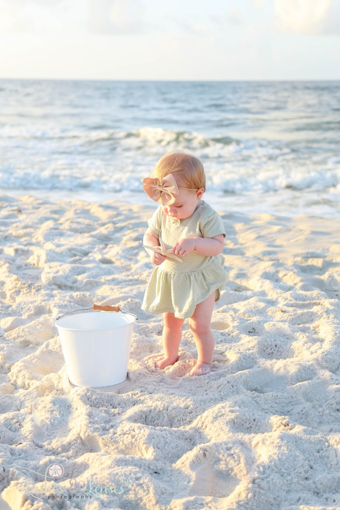 Baby girl standing in the sand with a sand bucket and the water behind her at Johnsons Beach in Perdido Key Florida