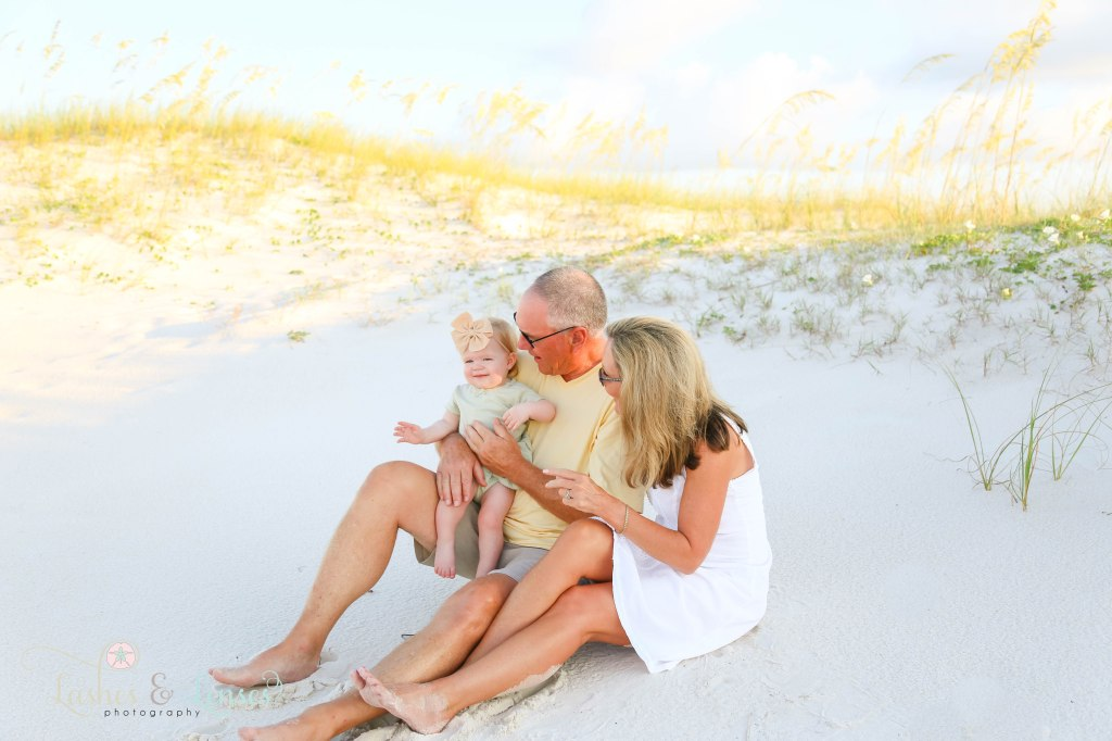 Grandparents sitting in the sand with their baby granddaughter sitting on grandpa's lap with the sand dunes and sea oats behind them at Johnsons Beach in Perdido Key Florida