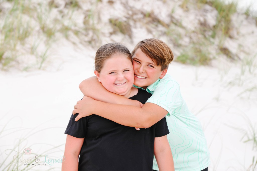 Pre-teen brother and sister, with the brother hugging sisters neck at Johnsons Beach in Perdido Key Florida