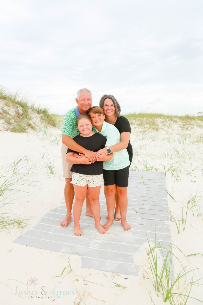 Mom and dad holding their son and daughter and standing on a washed up boardwalk at Johnsons Beach in Perdido Key Florida