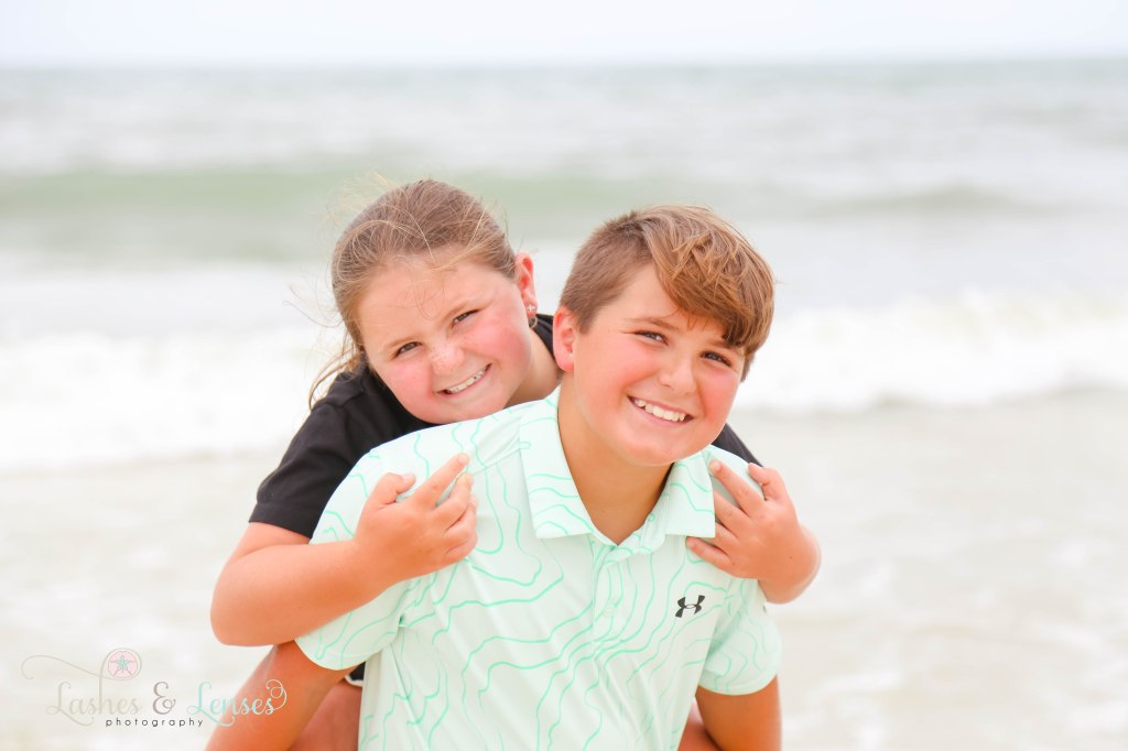 Sister on bothers back down by the water at Johnsons Beach in Perdido Key Florida