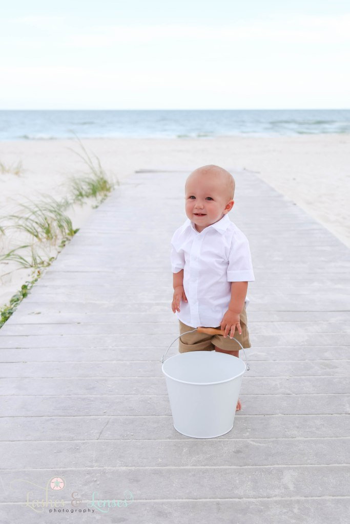 Young boy with bucket standing on a boardwalk at Johnsons Beach in Perdido Key Florida