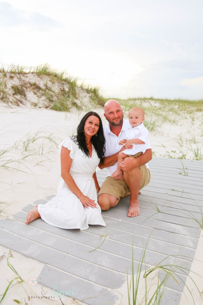 Grandparents sitting on the boardwalk with their young grandson at Johnsons Beach in Perdido Key Florida