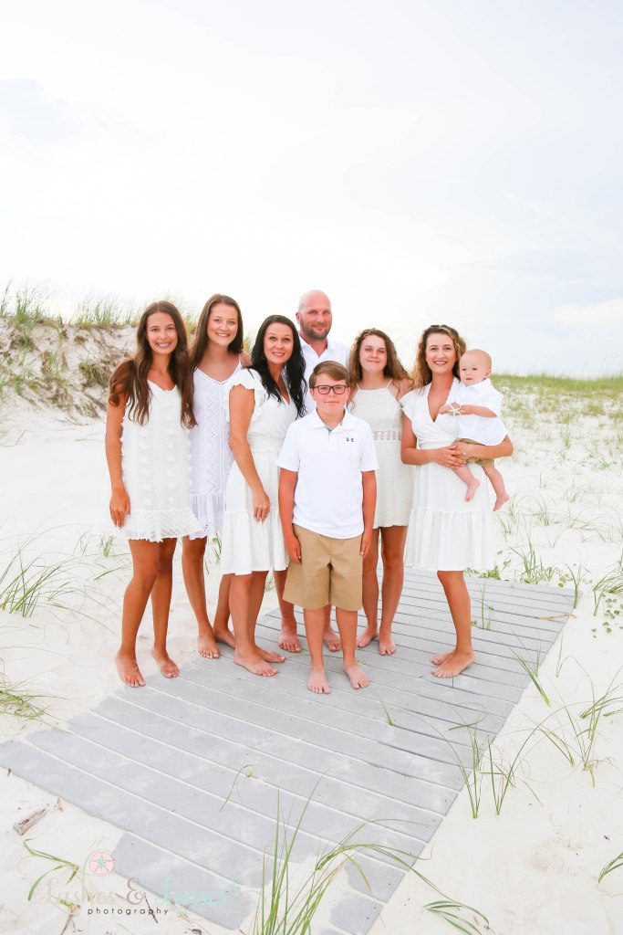 Extended family standing on a washed up palm tree at Johnsons Beach in Perdido Key Florida