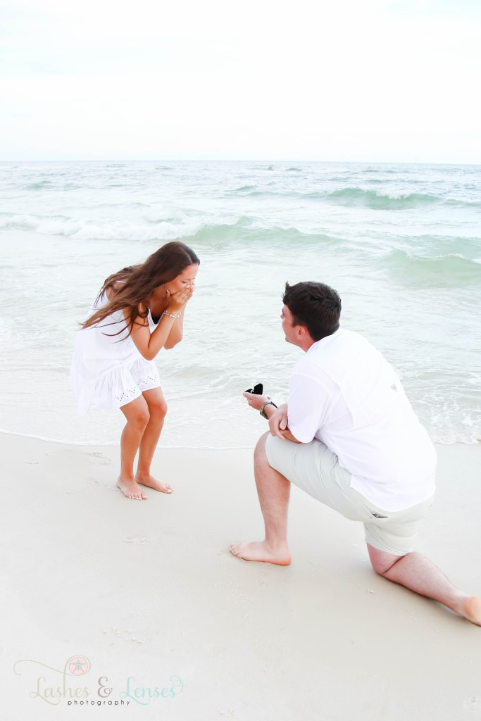 Young man proposing to girlfriend down by the water edge, with the ring still in the box at Johnsons Beach in Perdido Key Florida