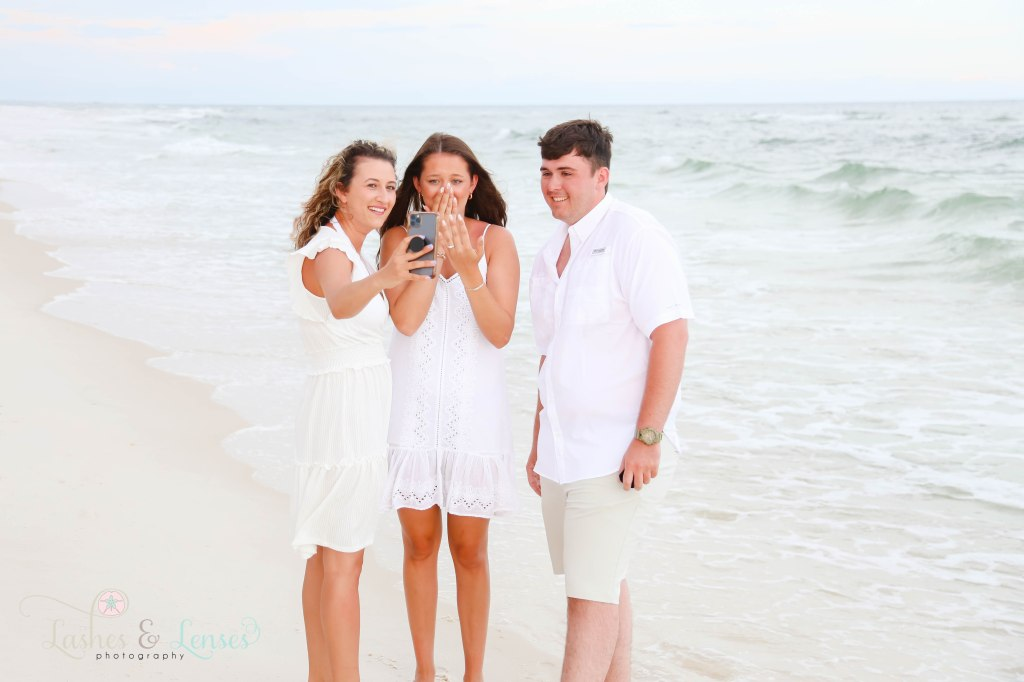 Newly engaged couple with her sister holding the phone so Dalton's family can be a part of the engagement at Johnsons Beach in Perdido Key Florida