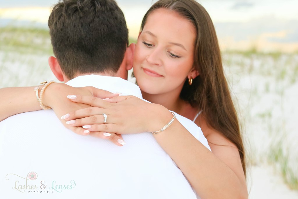A close up of the young lady hugging her new finance's neck and showing off the ring at Johnsons Beach in Perdido Key Florida