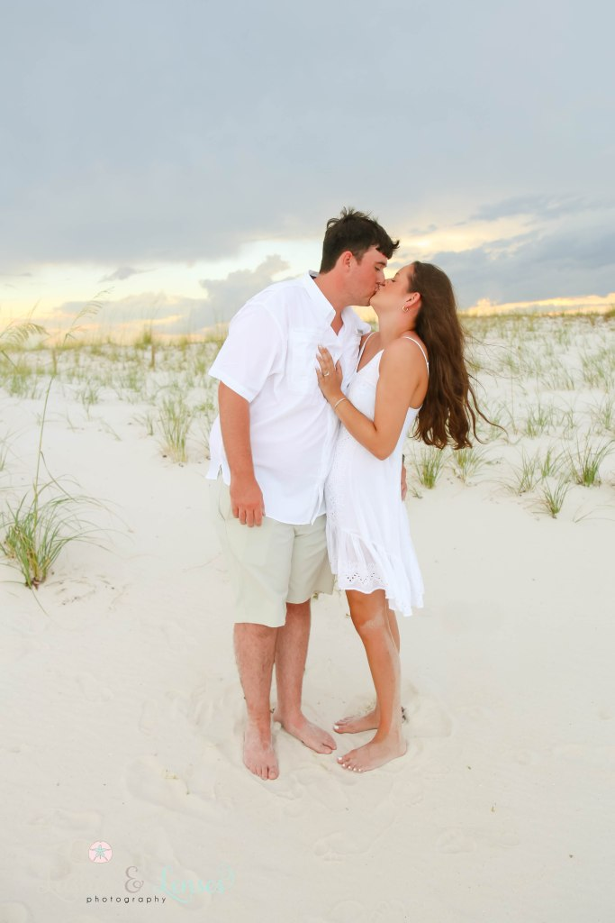 Couple kissing with the sunset behind them at Johnsons Beach in Perdido Key Florida