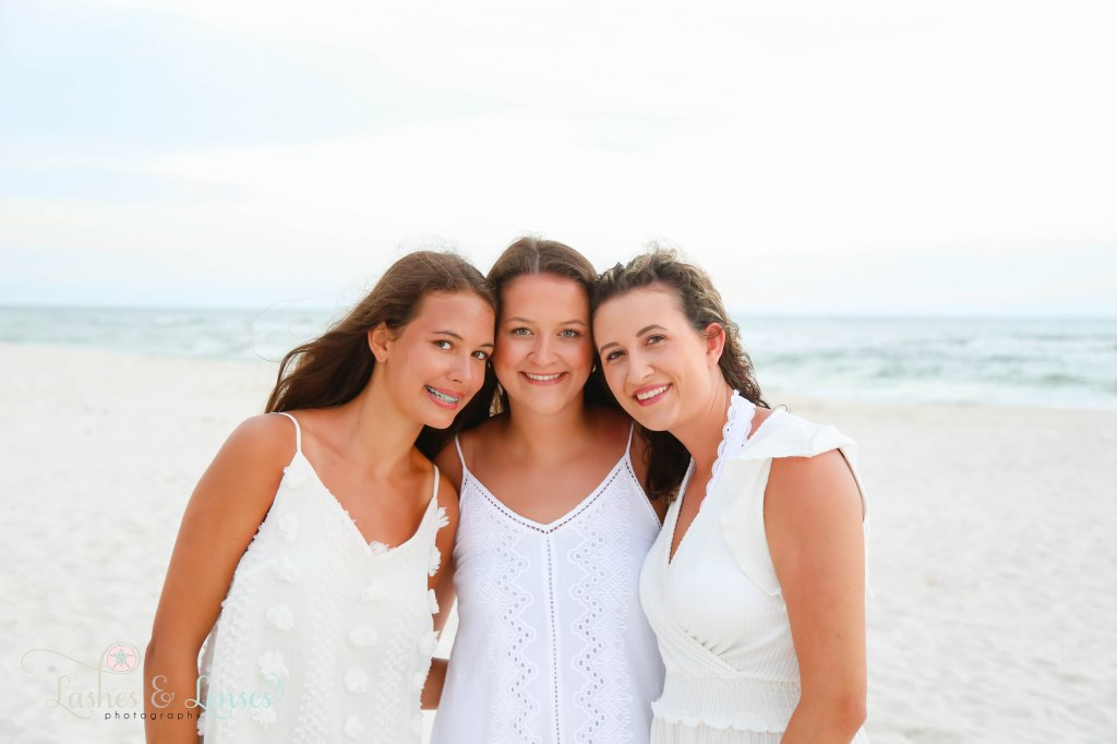 Three teen and adult sisters huddled together at Johnsons Beach in Perdido Key Florida