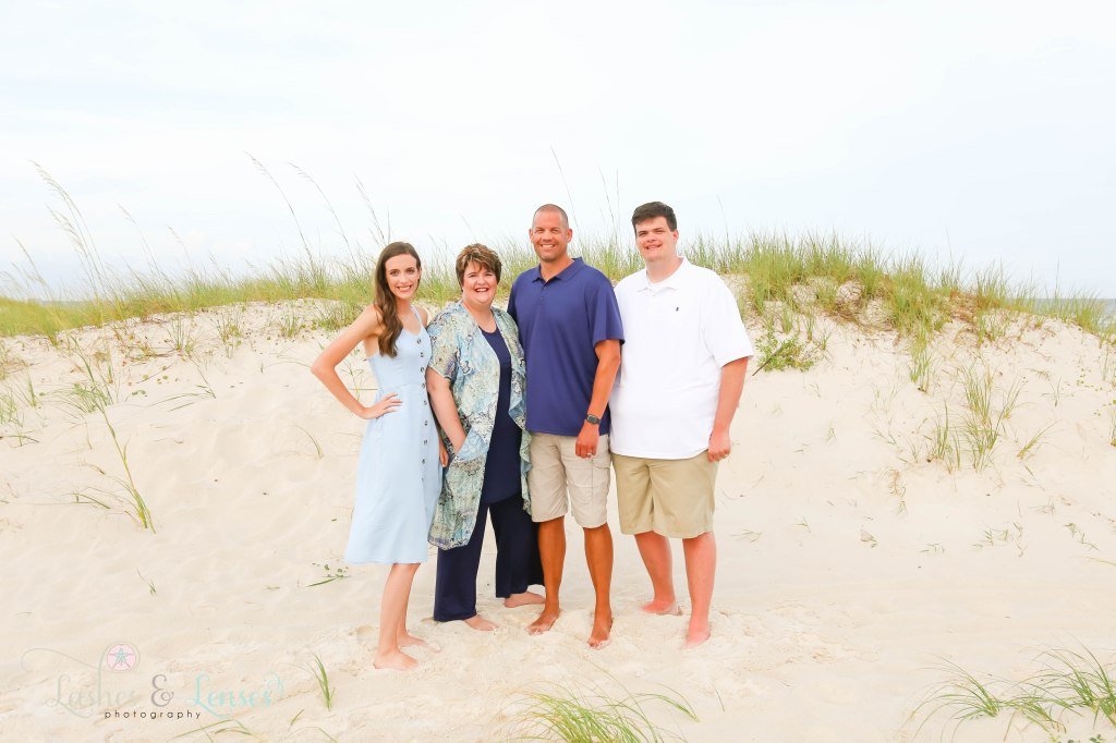 Mom, Dad, adult son and adult daughter standing next to the sand dunes at Johnsons Beach in Perdido Key Florida