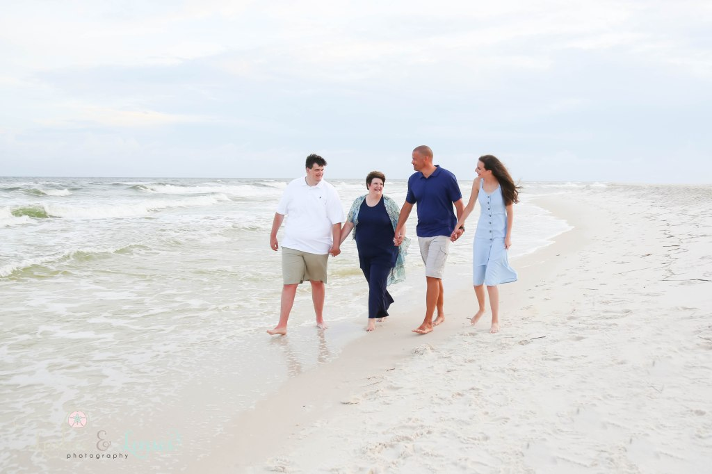 Family walking hand in hand and looking at each other down by the water at Johnsons Beach in Perdido Key Florida