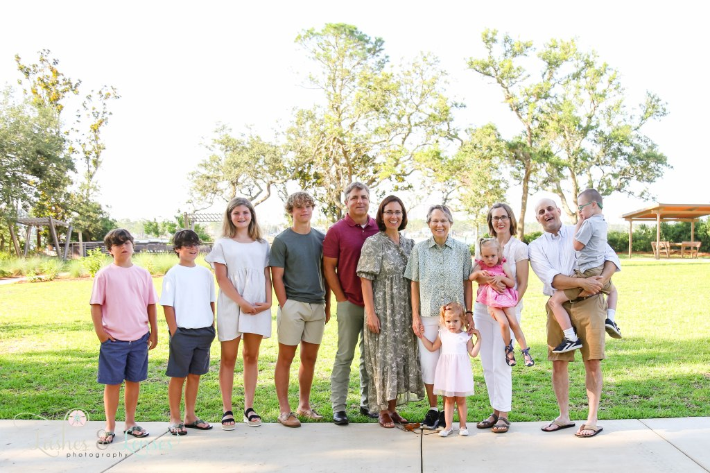 Large family with grandma and her two sets of children and their spouses and her grandchildren at Innerarity Point Park in Pensacola, Florida
