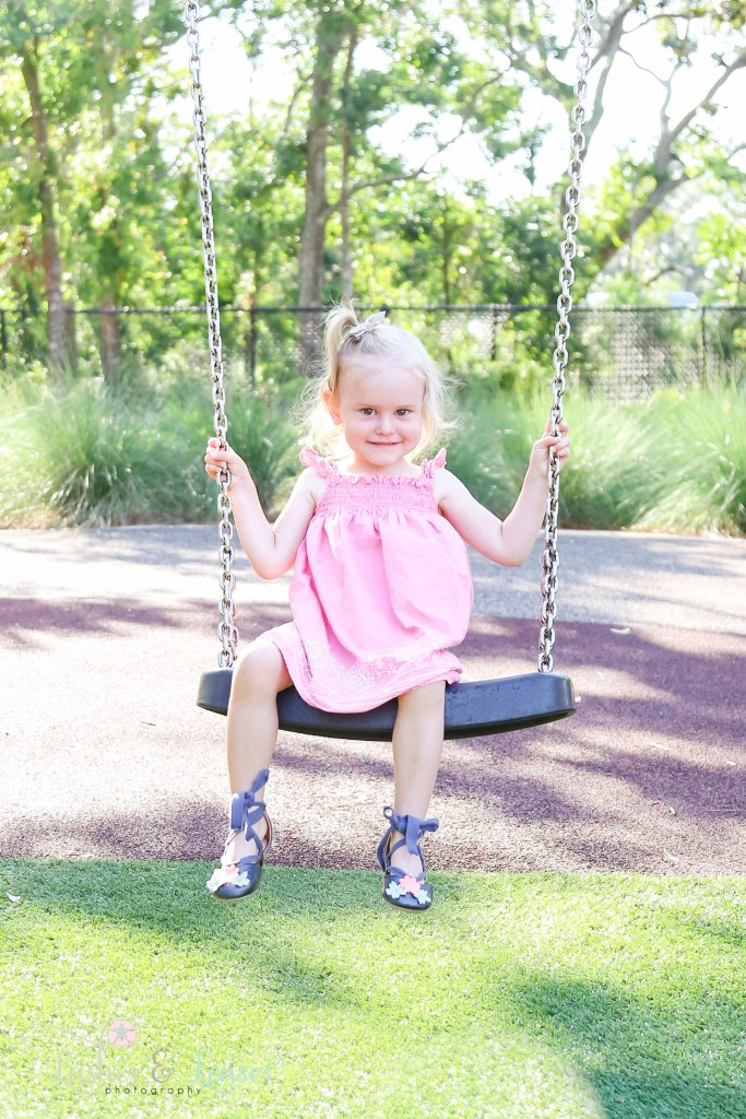 Toddler girl swinging on a big swing at Innerarity Point Park in Pensacola, Florida