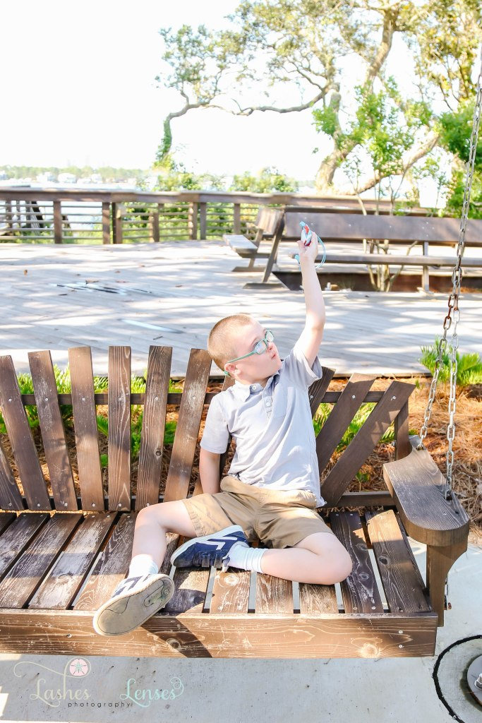 Toddler boy playing with imaginary airplane and sitting on a swinging chair at Innerarity Point Park in Pensacola, Florida