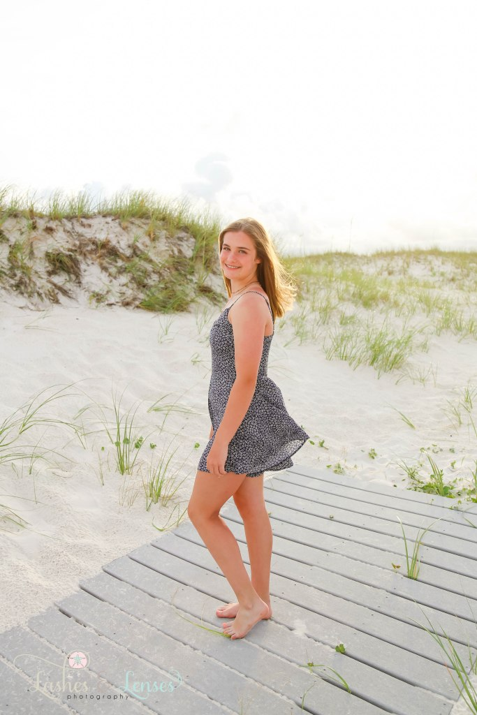 Teen girl standing on a washed up boardwalk at Johnsons Beach in Perdido Key Florida