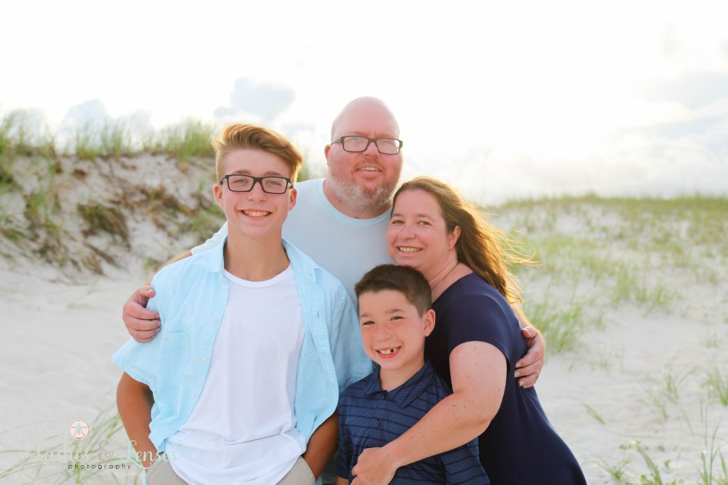 Mom and Dad huddling close with their two sons at Johnsons Beach in Perdido Key Florida