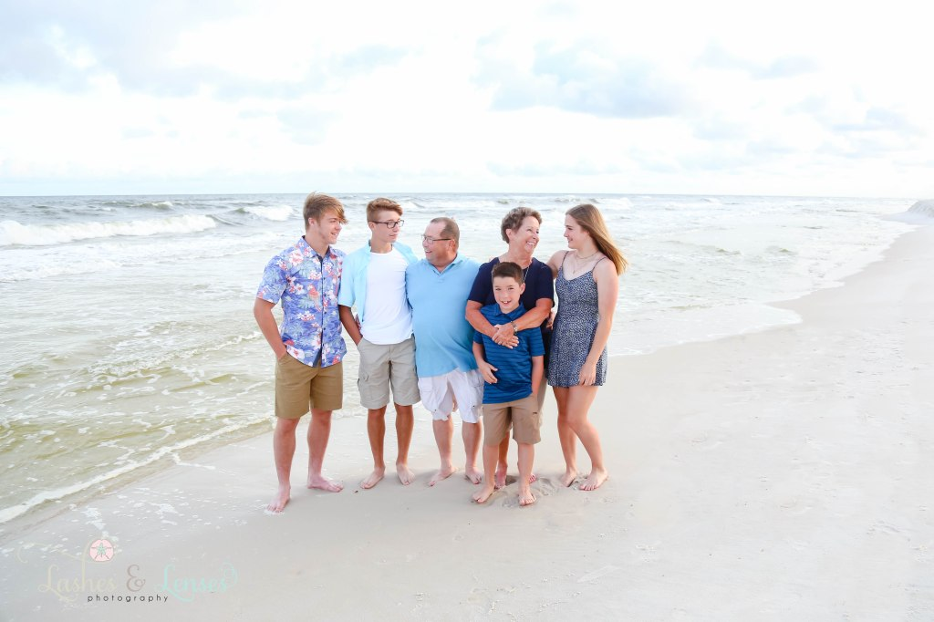 Grandparents standing with their grandchildren next to the water at Johnsons Beach in Perdido Key Florida