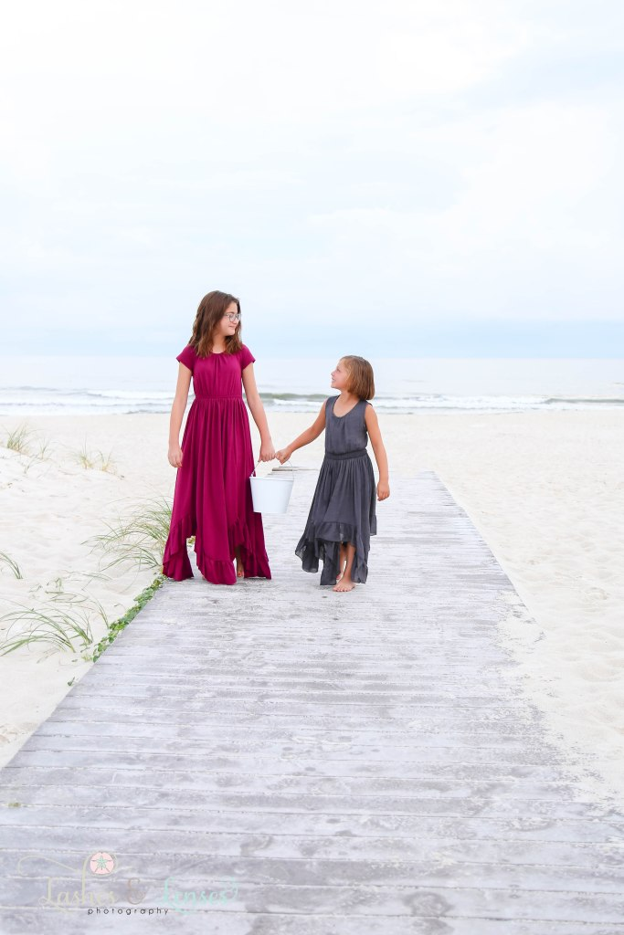 Sisters walking back up the boardwalk with the water behind themat Johnsons Beach in Perdido Key Florida
