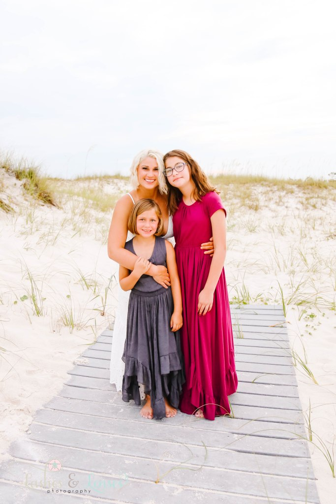 Mom standing and hugging her two daughters on washed up boardwalk at Johnsons Beach in Perdido Key Florida