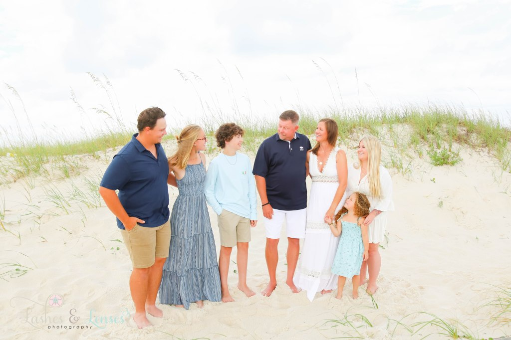 Family with several children all looking at each other and standing next to the sand dunes at Johnsons Beach in Perdido Key Florida