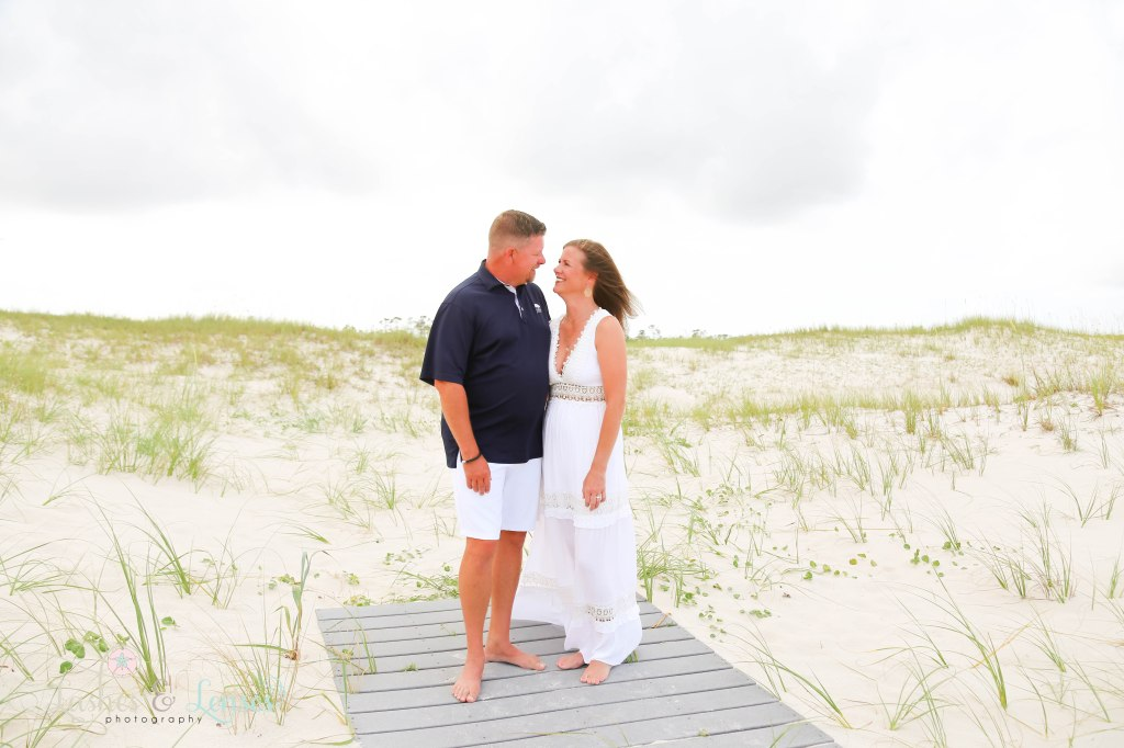 Husband and wife looking into each others eyes and standing on a washed up boardwalk at Johnsons Beach in Perdido Key Florida