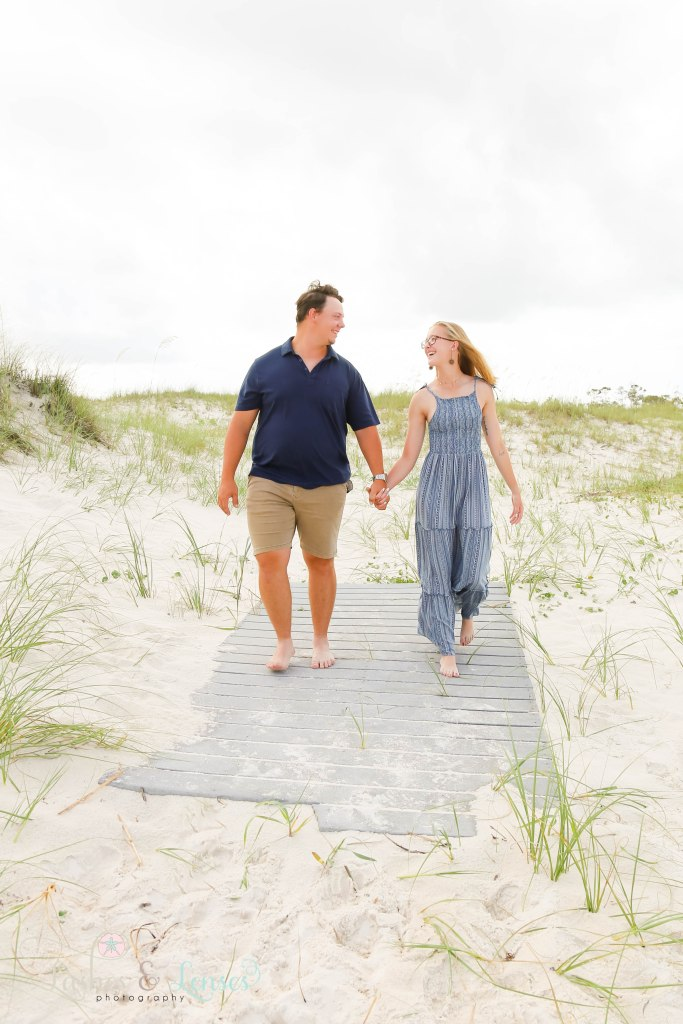 Young couple walking down the boardwalk hand in hand at Johnsons Beach in Perdido Key Florida