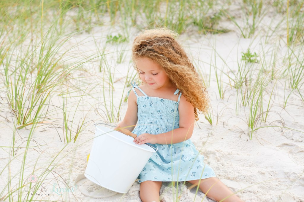 Toddler girl looking into a sand bucket sitting in the sand with sea grass all around her at Johnsons Beach in Perdido Key Florida