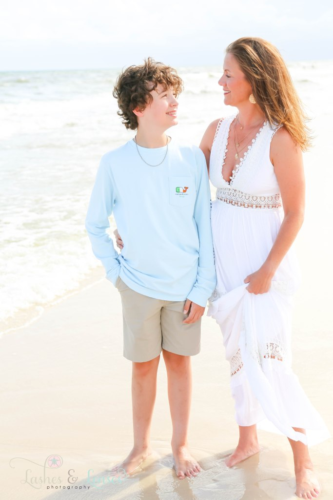 Mom and pre-teen son standing down by the water at Johnsons Beach in Perdido Key Florida