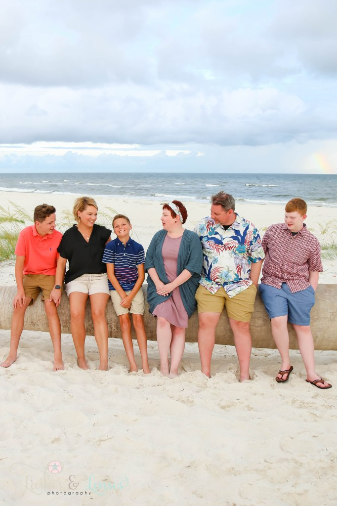 Two family sitting on a washed up palm tree with a rainbow behind them at Johnsons Beach in Perdido Key Florida