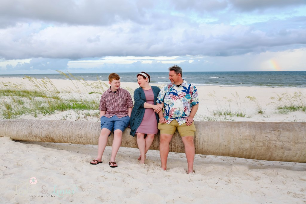 Mom, Dad and teen son sitting on a washed up palm tree with a rainbow behind them at Johnsons Beach in Perdido Key Florida