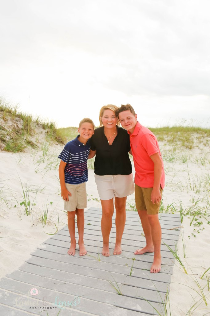 Mom and her two sons standing on the boardwalk with the sunset behind them at Johnsons Beach in Perdido Key Florida