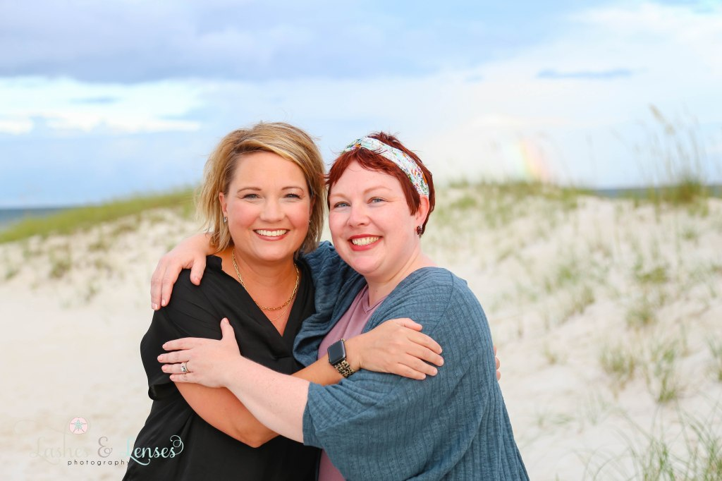 Two Adult best friends with the water and a rainbow behind them at Johnsons Beach in Perdido Key Florida