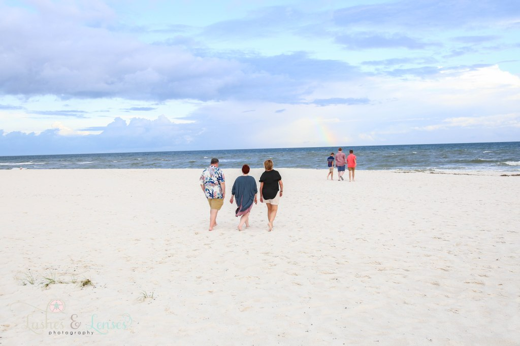 Two sets of friends family's walking down towards the water with a rainbow behind them at Johnsons Beach in Perdido Key Florida