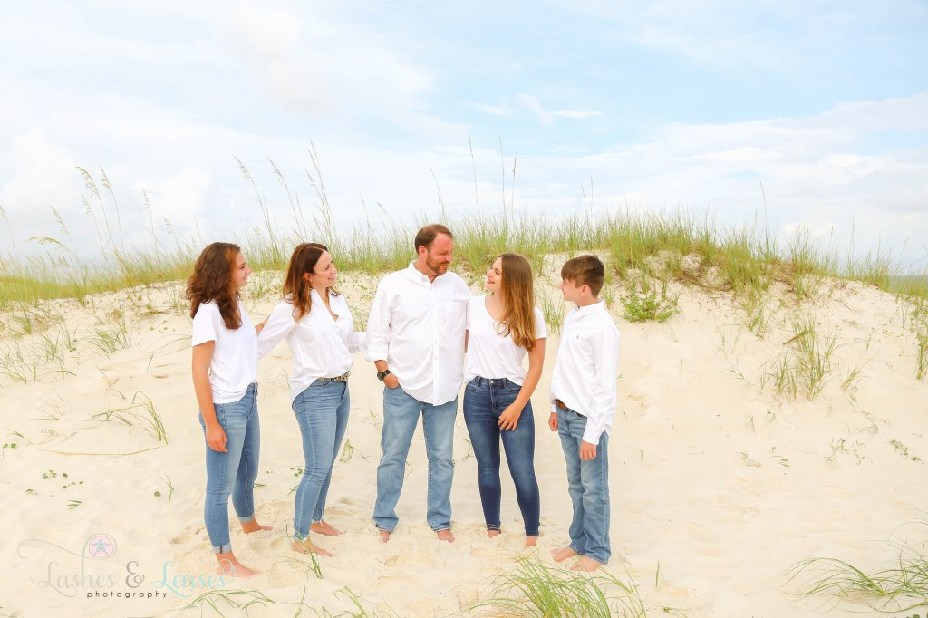 Mom, Dad, two teen daughters and young teen son looking at each other next to the sand dunes at Johnsons Beach in Perdido Key Florida