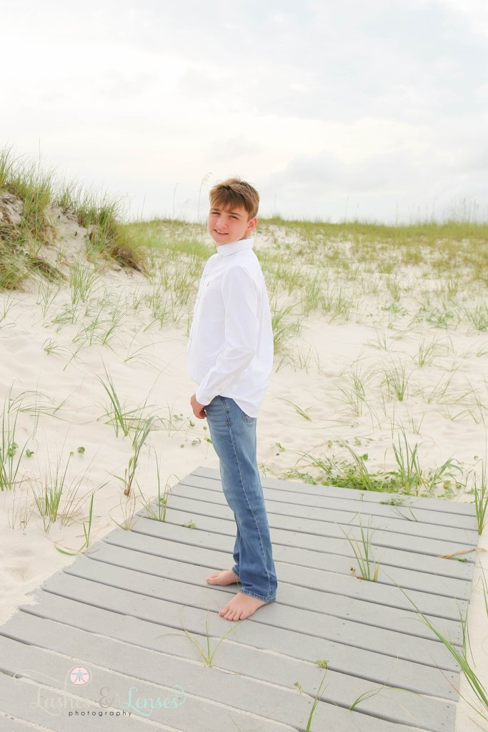 Young teen boy standing on a washed up boardwalk in the sand dunes at Johnsons Beach in Perdido Key Florida