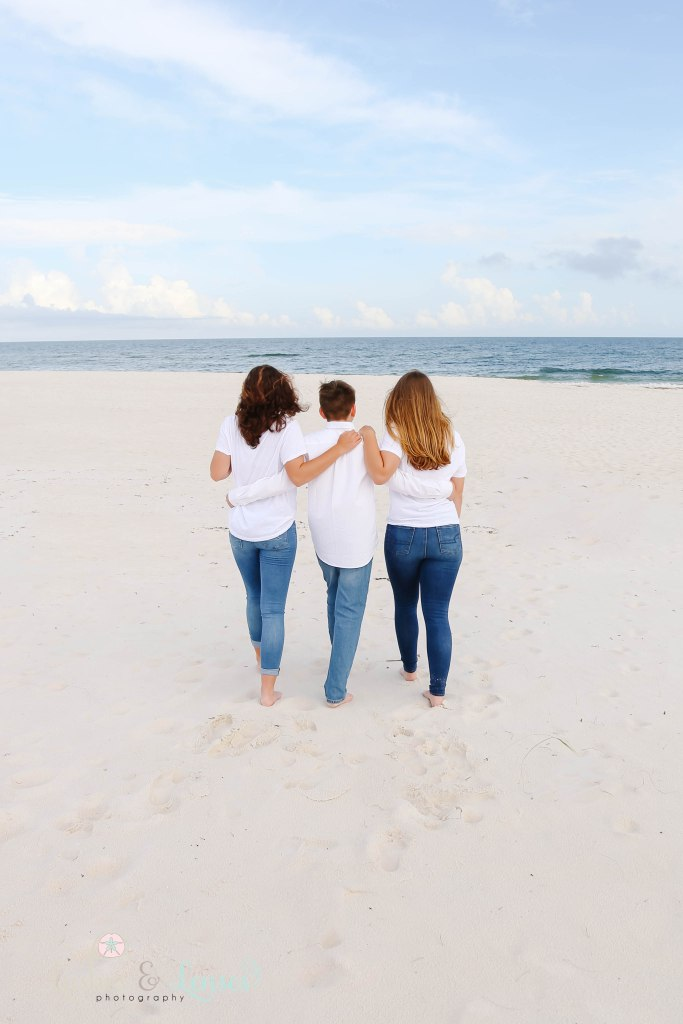 Brother and sisters walking towards the water with their hands on each others backs at Johnsons Beach in Perdido Key Florida