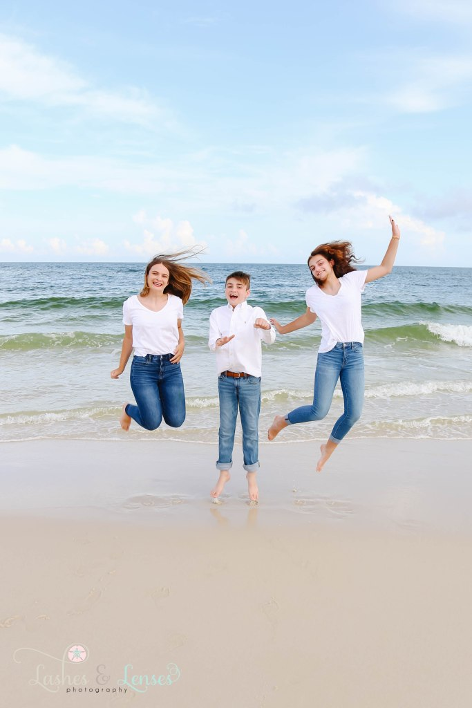 Two teen sisters and young teen brother jumping in the air down by the waters edge at Johnsons Beach in Perdido Key Florida