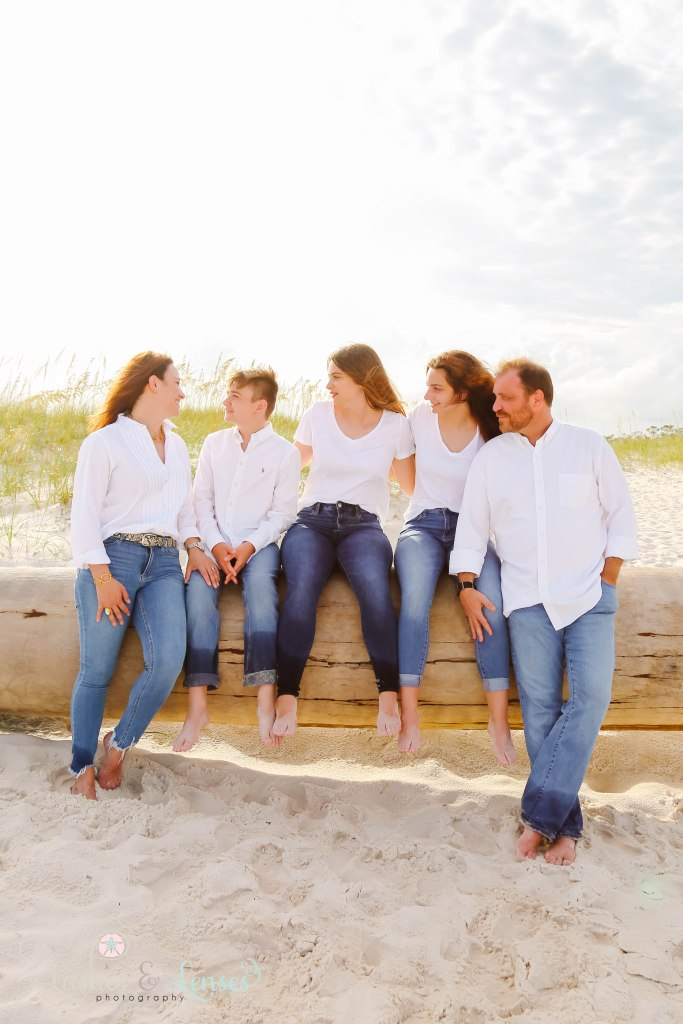 Family of five sitting on a washed up sand dune with the sea oats behind them at Johnsons Beach in Perdido Key Florida